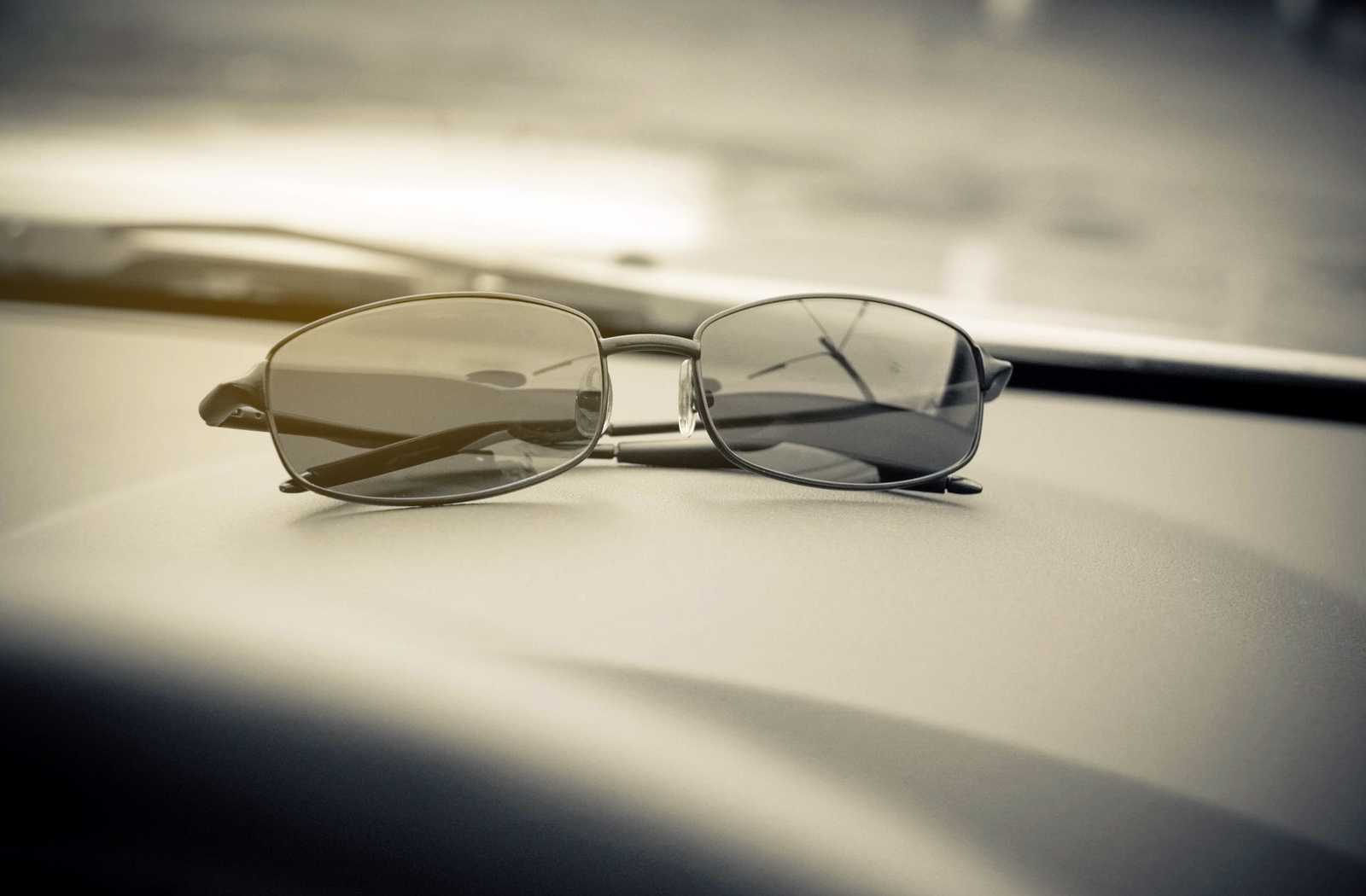 black and white shades quality sunglasses folded and resting on a car dashboard.