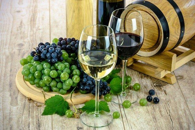 Grapes and two wine glasses next to a small barrel
