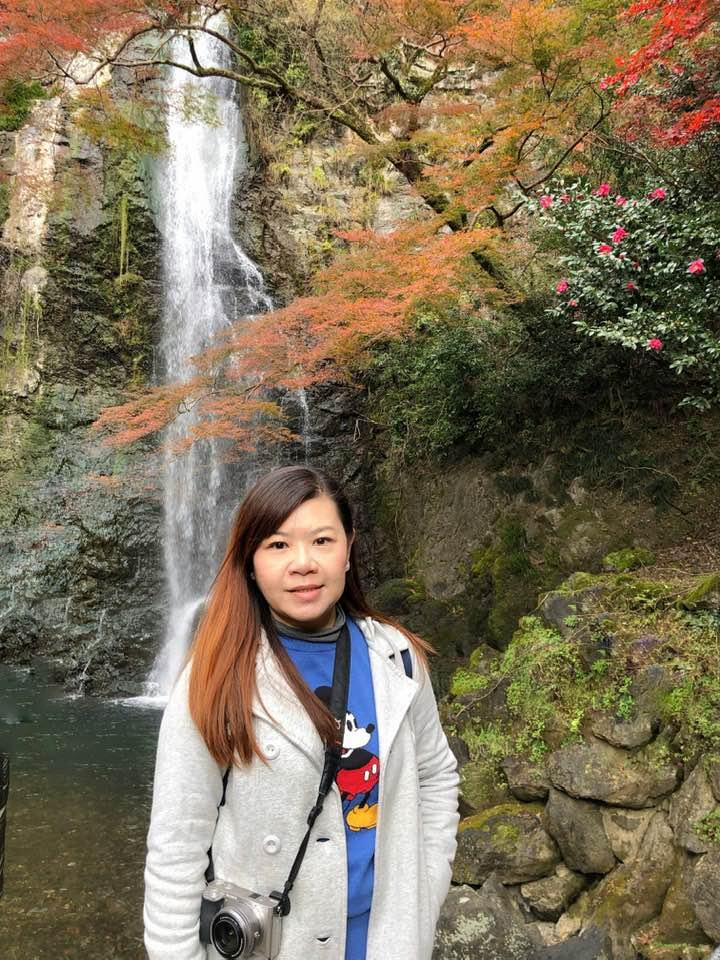 A person standing next to a waterfall  Description automatically generated
