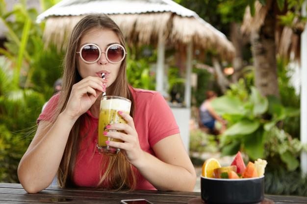 Mulher jovem feliz de férias tomando uma bebida fresca. mulher caucasiana atraente em tons redondos da moda bebendo coquetel não alcoólico Foto gratuita