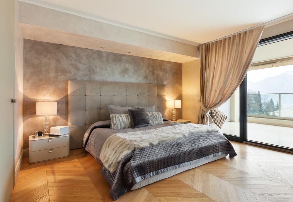 Um quarto clássico com uma cama de estofado, duas luminárias e uma cortina grande na janela.