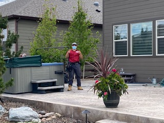 Absolute tech smiles and gives thumbs-up beside a newly-installed hot tub on stamped concrete patio with homes in the background