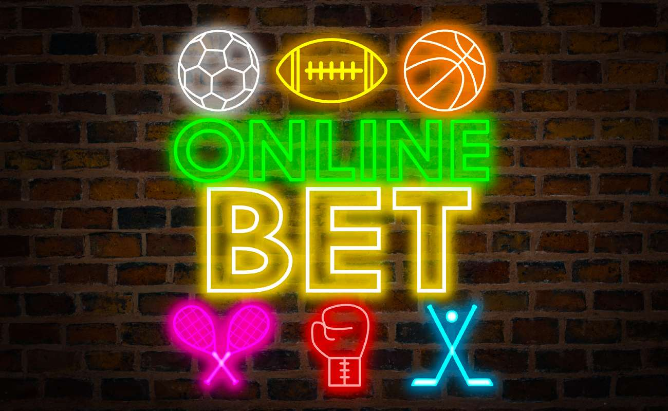 Online bet neon sign with different sports logos around it