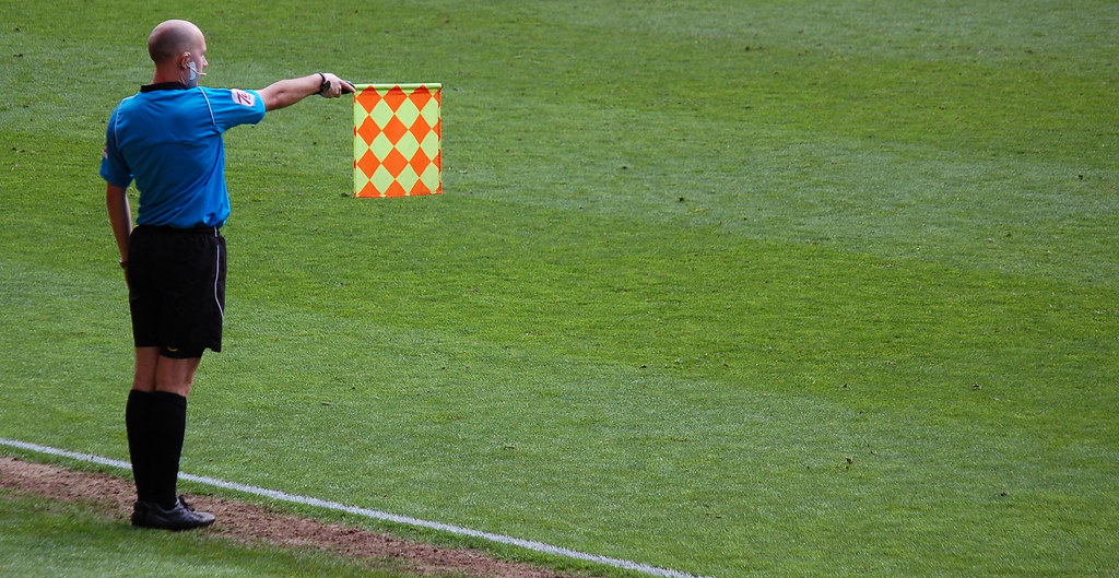Assistant referee flagging for offside (Why Offsides in Soccer?)