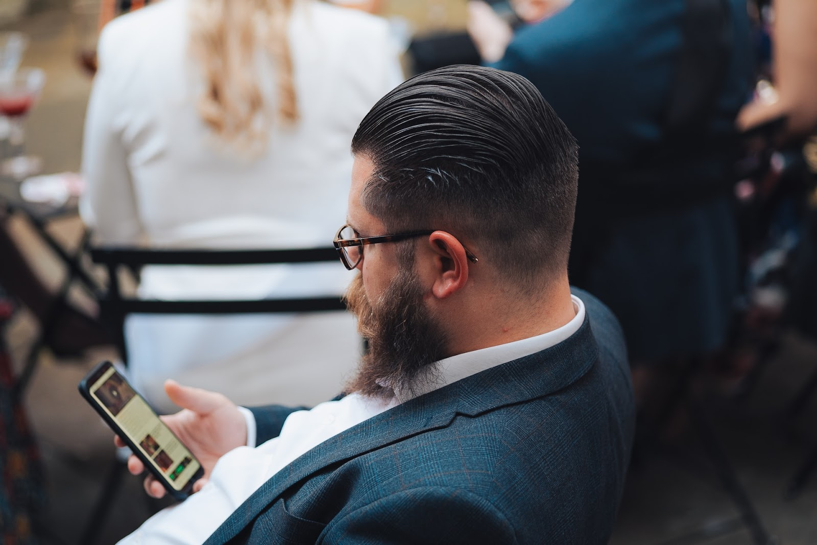 a man in a suit sits in a chair and stares at his phone