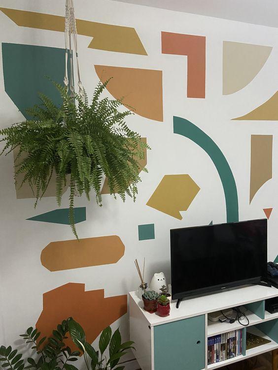 Sala com parede com desenhos geométricos coloridos.