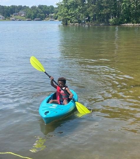 Dr Eva's son kayaking in a lake