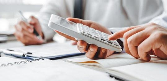 Executivo usando calculadora para fazer a prestação de contas da administradora