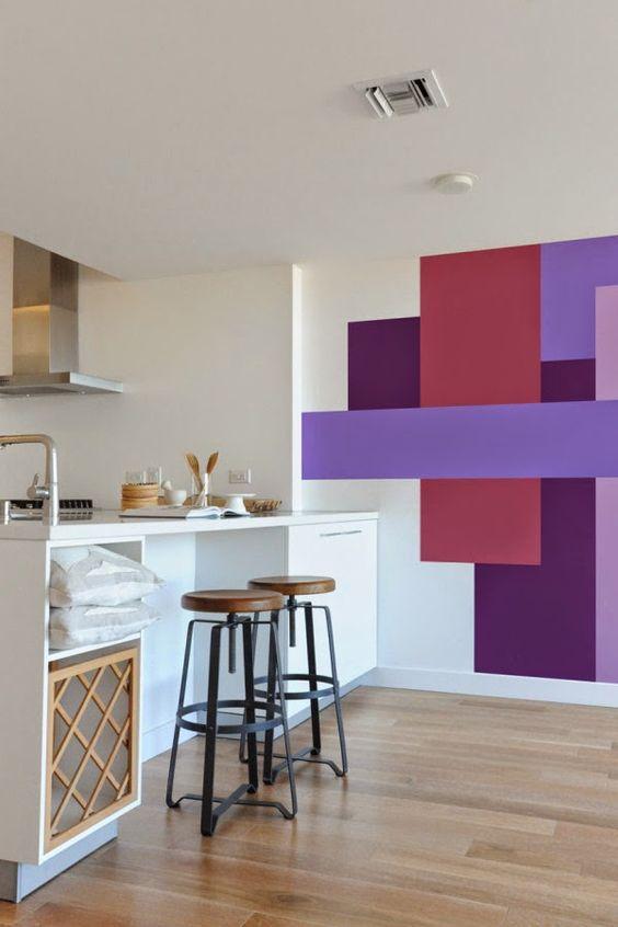 Cozinha com parede lateral com pintura geométrica de cores fortes, armários brancos, bancos marrom e piso de madeira.