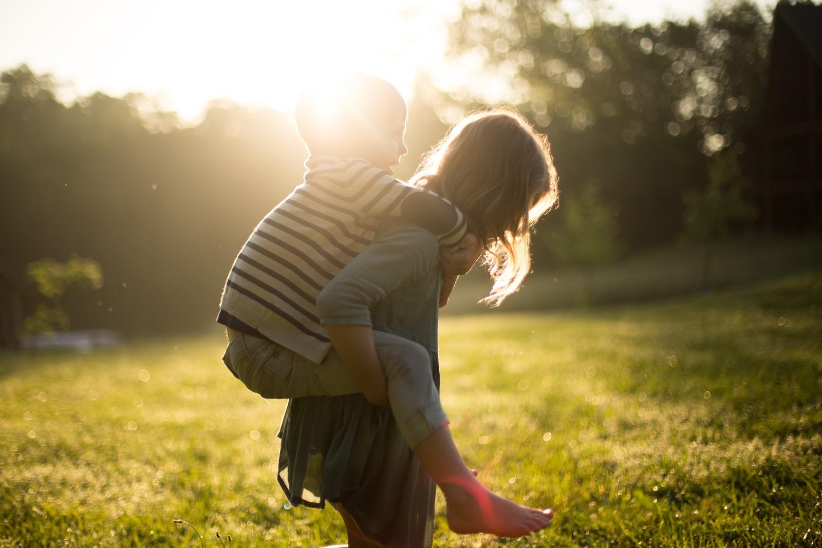 Uma menina segurando uma criança na garupa com a luz do sol forte em ambos.