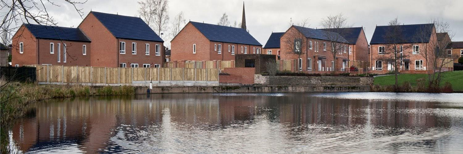 A group of houses next to a body of water  Description automatically generated with medium confidence