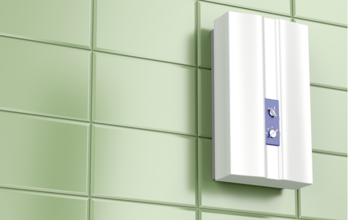 tankless water heater on green tiled wall