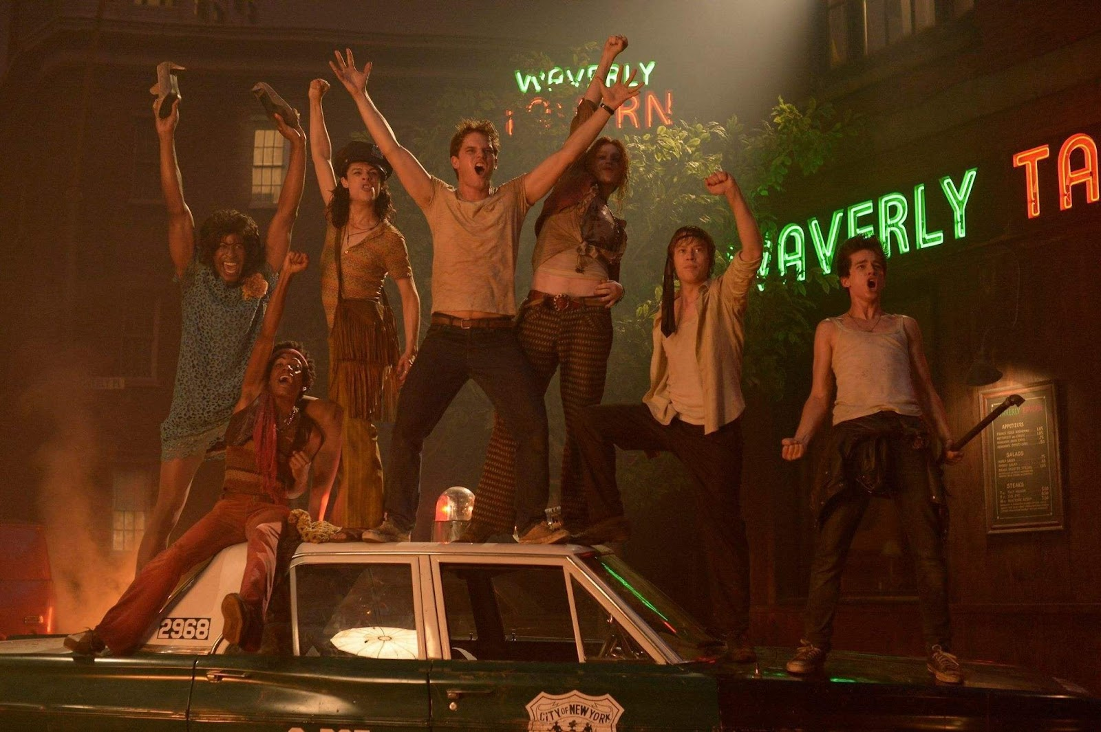Still from Stonewall (2015). A gang of seven young people stand on top of an empty police car on a darkened street, raising their fists in the air. A fire is burning behind them.