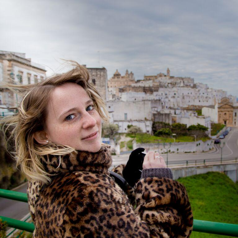 Image description: Abi is seen here at an external location. She is wearing a leopard print coat, her long, highlighted hair is wind swept and she is looking back at the camera with a hint of a smile. Abi is holding a smartphone and appears to be taking photographs of the scenery.