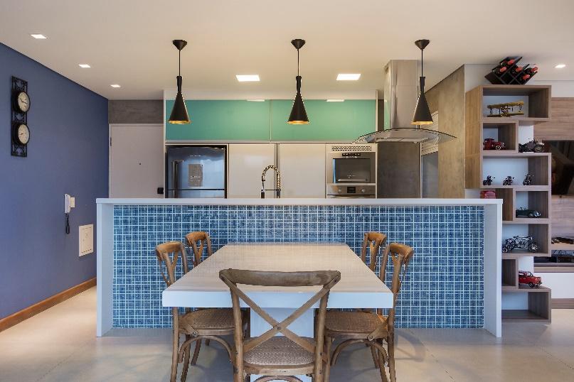 Ambiente com pastilha azul em baixo da bancada da cozinha, trazendo divisão para sala de jantar com mesa branca e cadeiras de madeira.