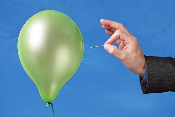 A pin being used to pop a green balloon