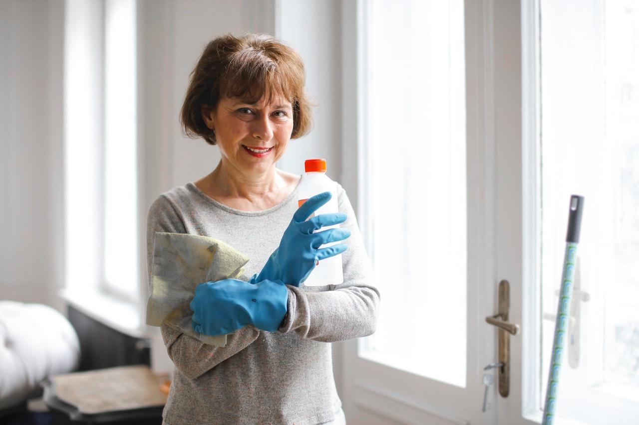 Uma mulher idosa segurando produtos de limpeza sorrindo para a foto.
