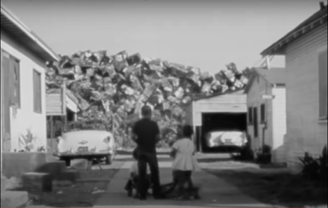 Felicia (1965). A wide shot of an alley between white panelled houses in Watts, LA. Standing in the middle with their backs to the camera are a man, and a smaller girl. They are looking towards a vast pile of scrapped cars that looms over the houses in the background.