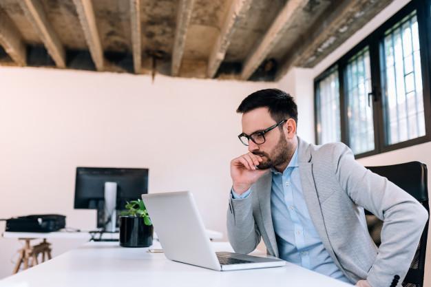 Serious businessman looking at laptop screen. Premium Photo