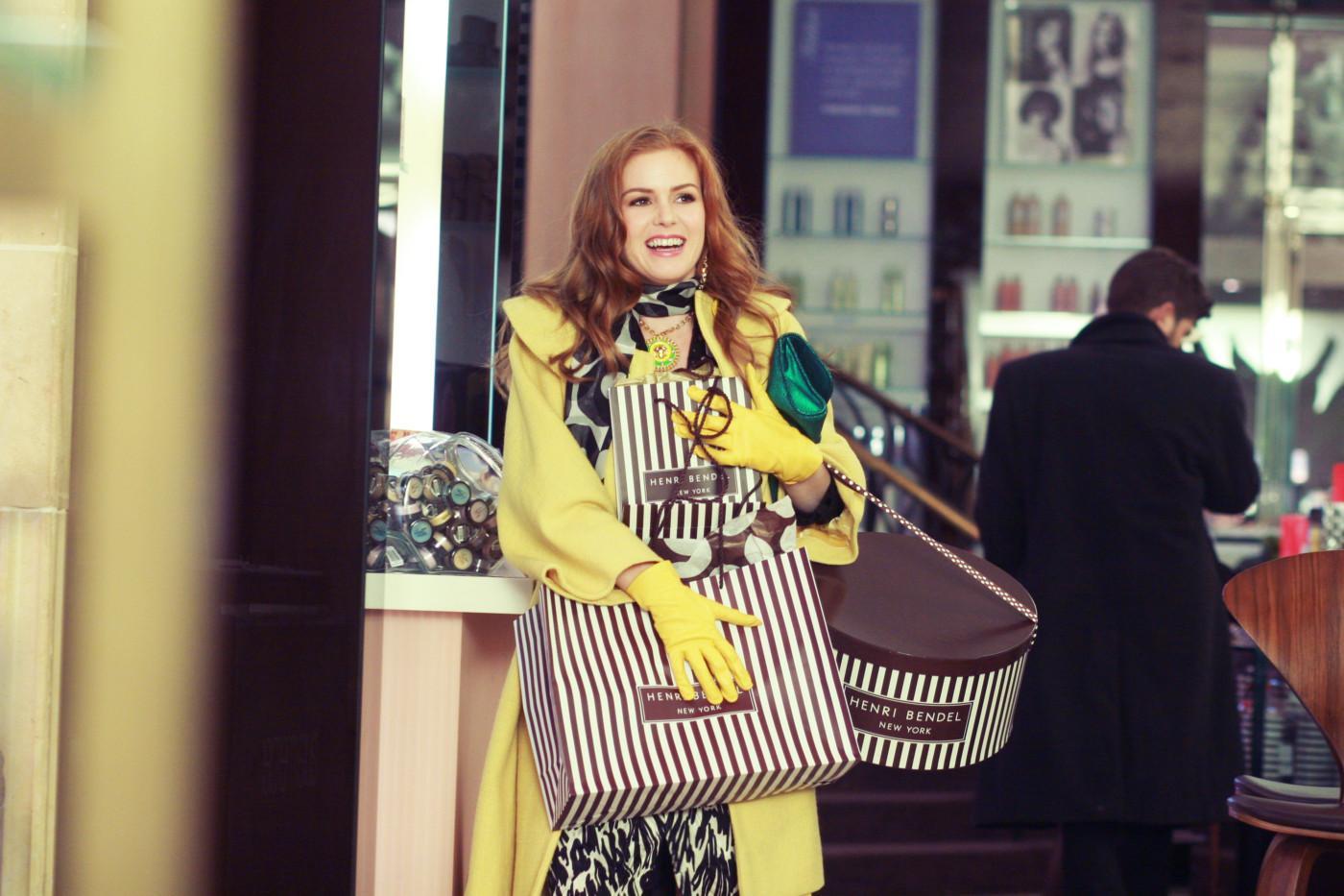 Mulher de casaco e luvas amarelas segurando sacolas brancas com listras marrons