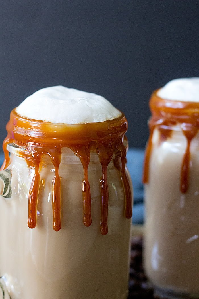 2 mason jars filled with caramel lattes with caramel dripping down sides & foam tops