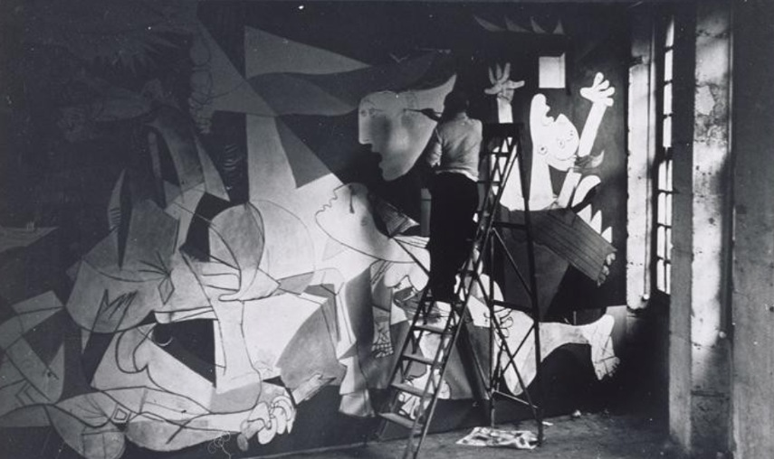A picture of Pablo Picasso applying finishing touches to Guernica