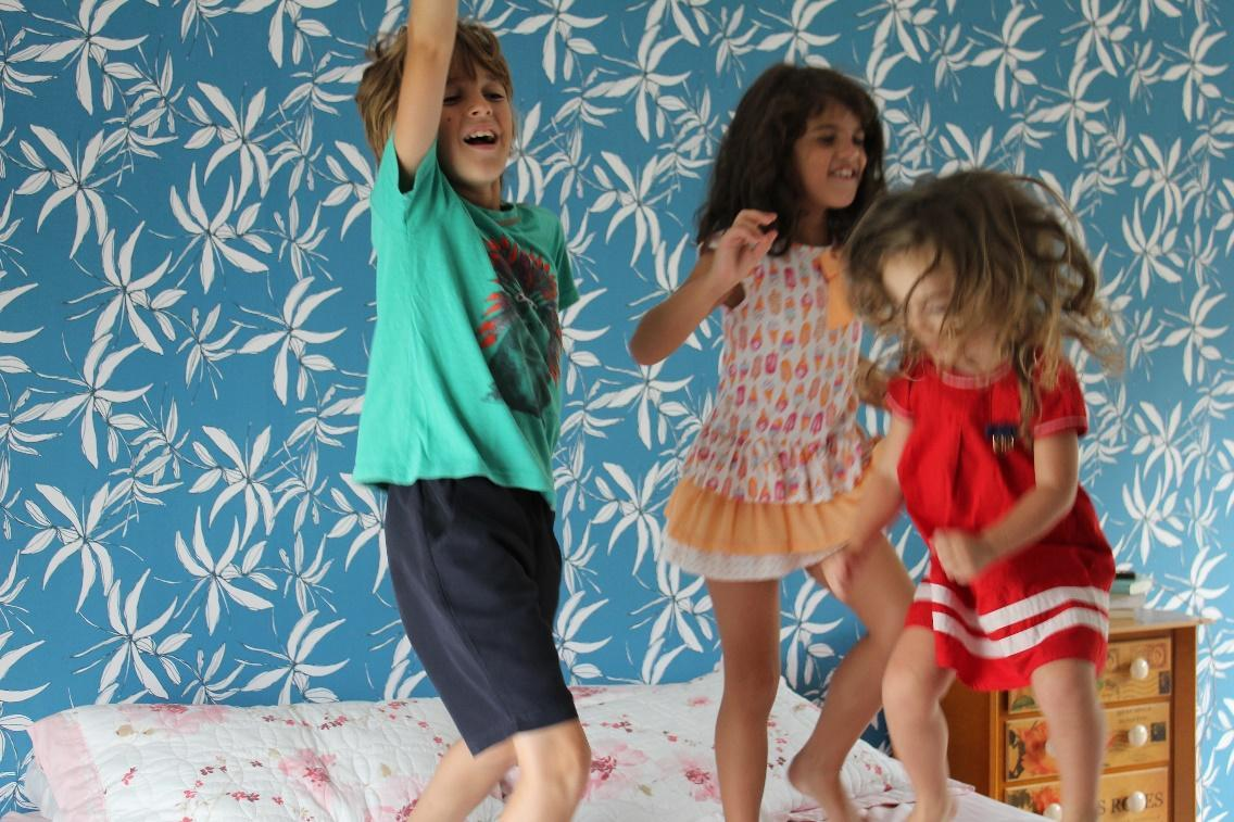 Kids having a dance off with kids bedding in the background.