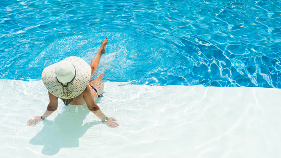 Woman in a hat sitting on the edge of a swimming pool with her foot in the water