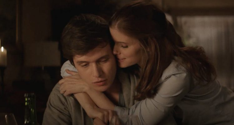 Nick Robinson and Kate Mara in A Teacher. Nick is sitting down, looking at the floor. Claire stands behind him with her arms wrapped around his shoulders, whispering into Nick's ear.