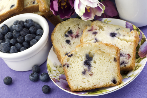 A slice of blueberry pound cake next to a small bowl of blueberries