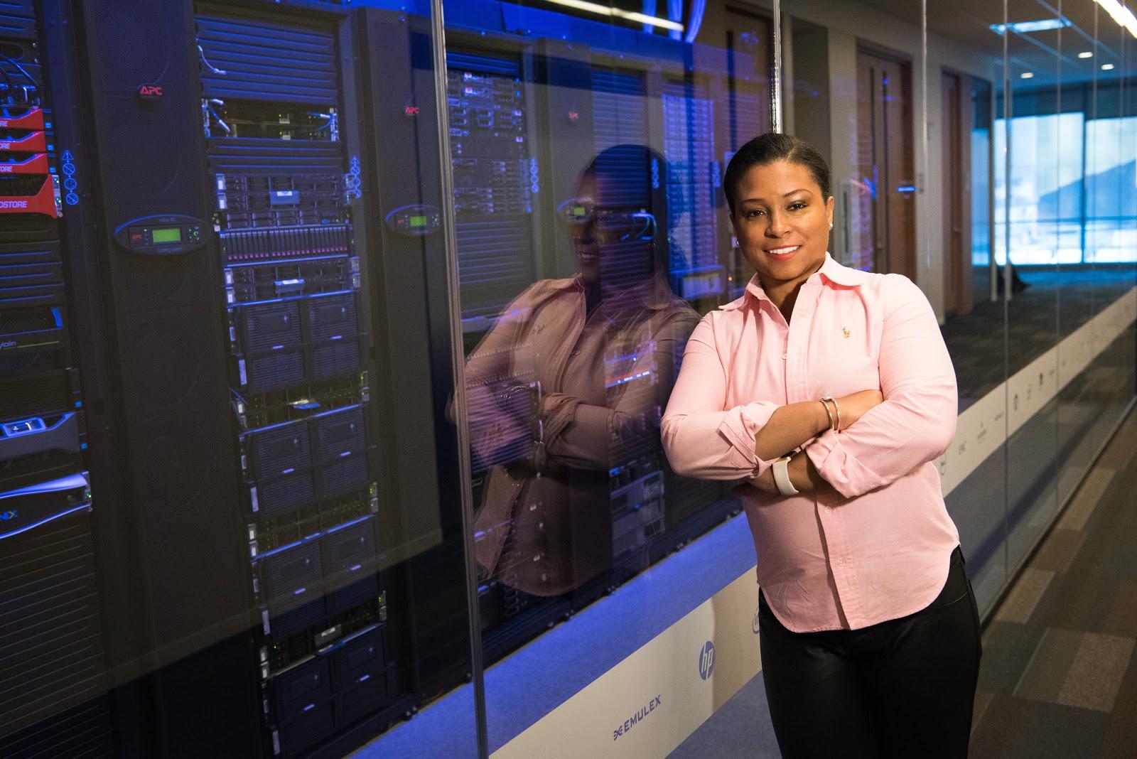 A woman leans against a server rack