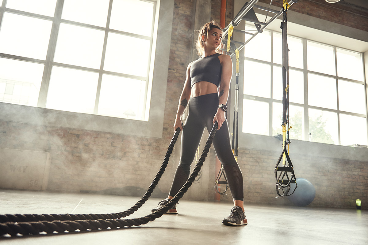 Woman working out with heavy ropes