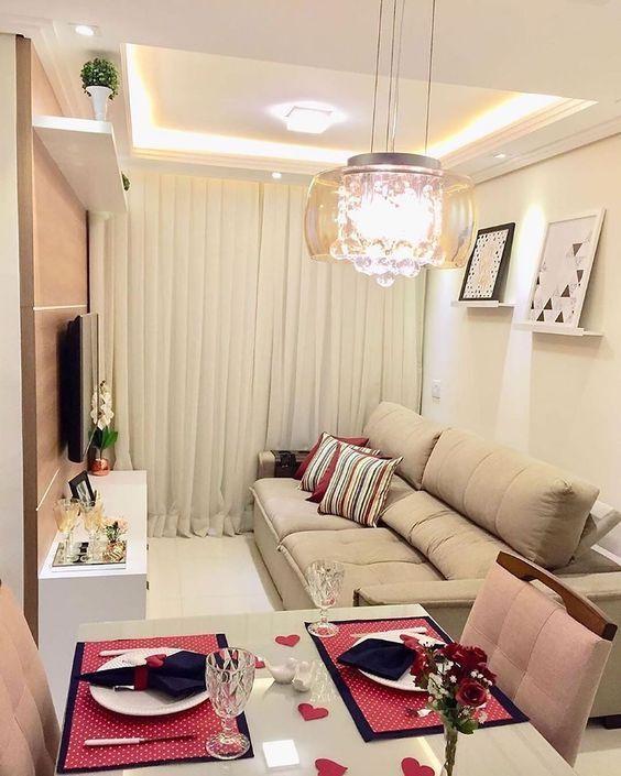 Sala com sofá grande creme, painel de TV marrom e branco, quadros decorativos, lustre e mesa de jantar.