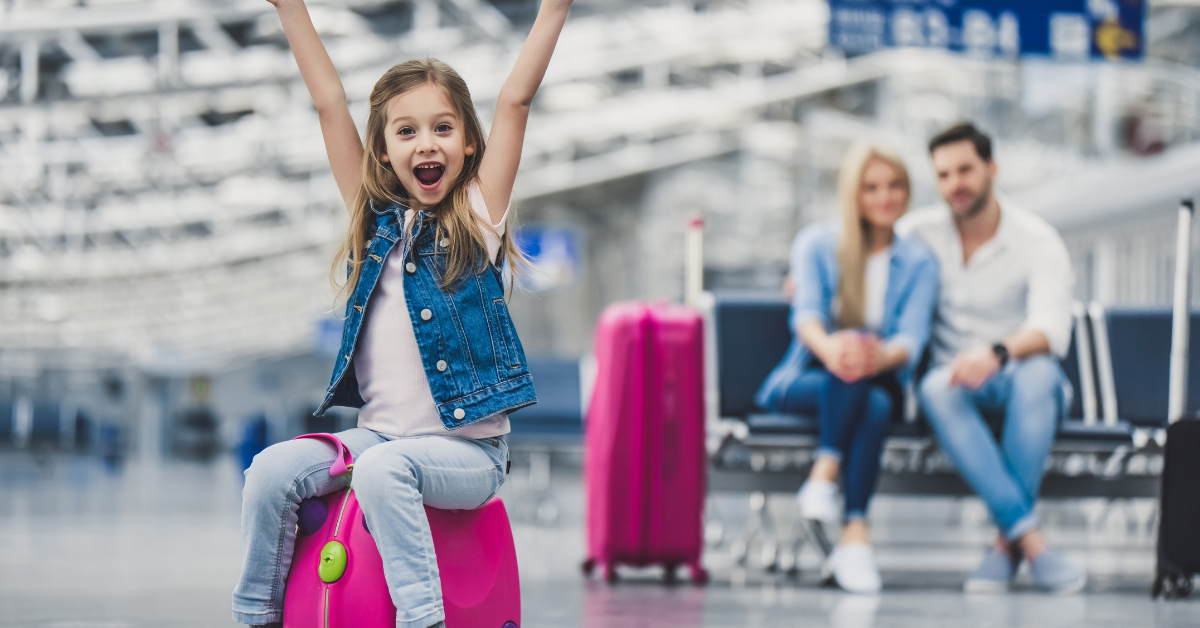 A girl and her parents waiting at the airport with the suitcases