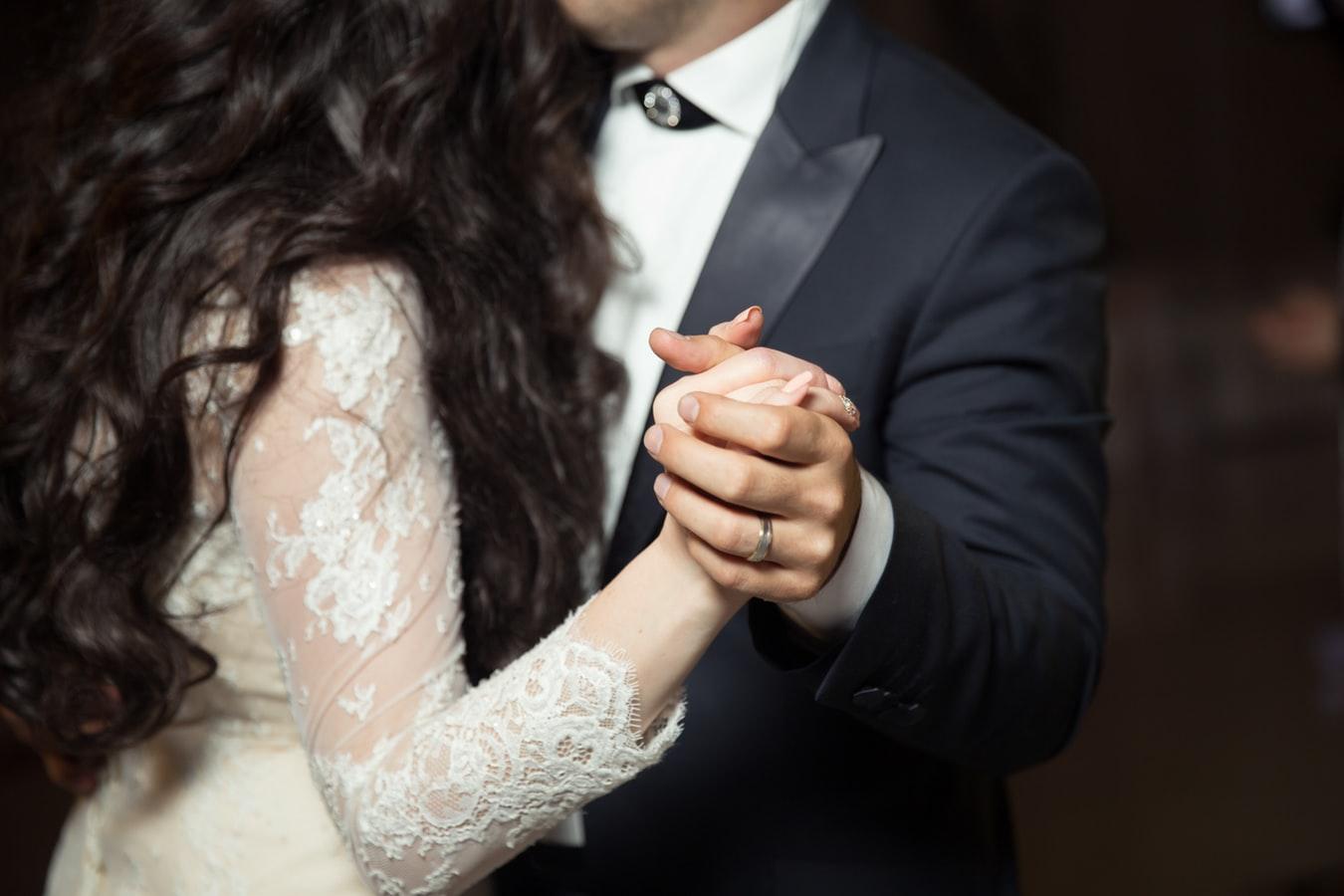 穿著新郎與新娘禮服的兩人翩翩起舞,交握的手指上戴著戒指。