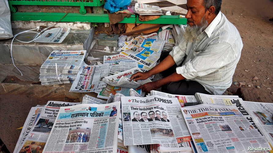 A vendor arranges newspapers with headlines about Supreme Court's verdict on a disputed religious site claimed by both majority…