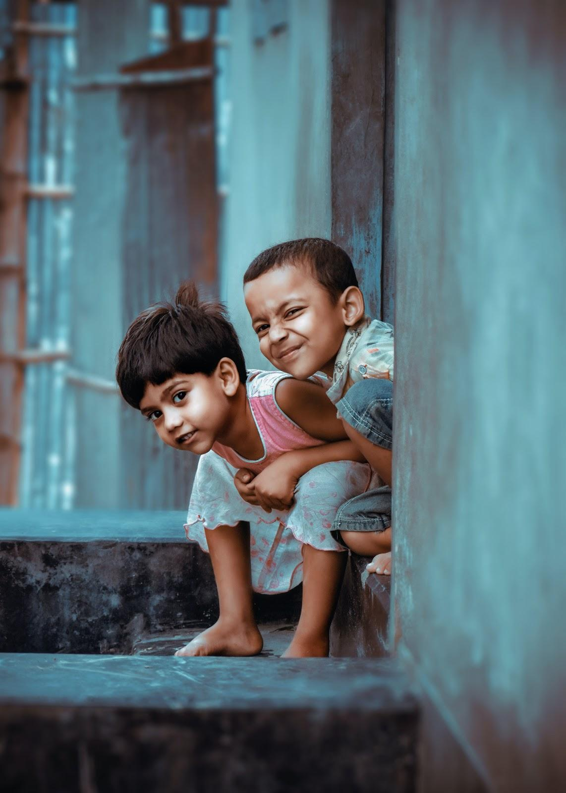 two children sitting outside the house, smiling at the camera