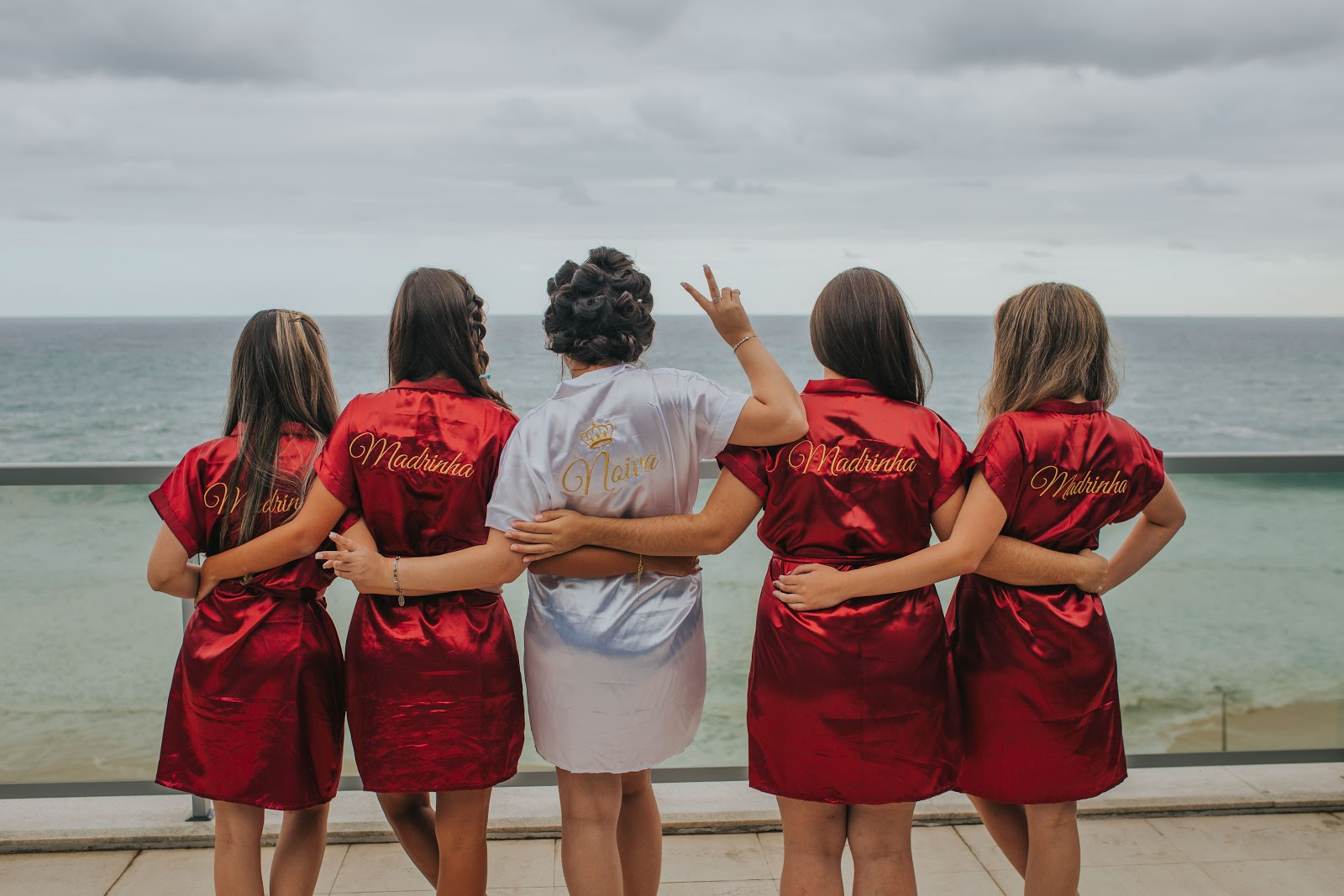 bride and bridesmaids in front of ocean