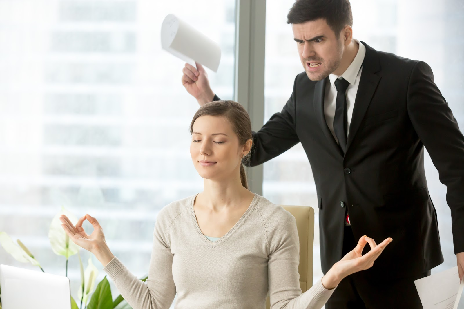 An angry man standing over a woman meditating