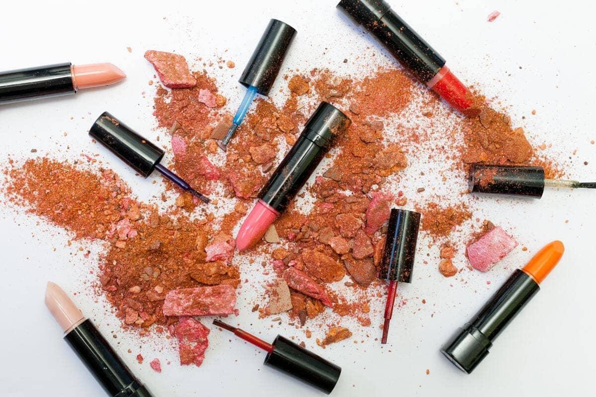 Dei rossetti e smalti di vari colori sparsi su una superficie bianca