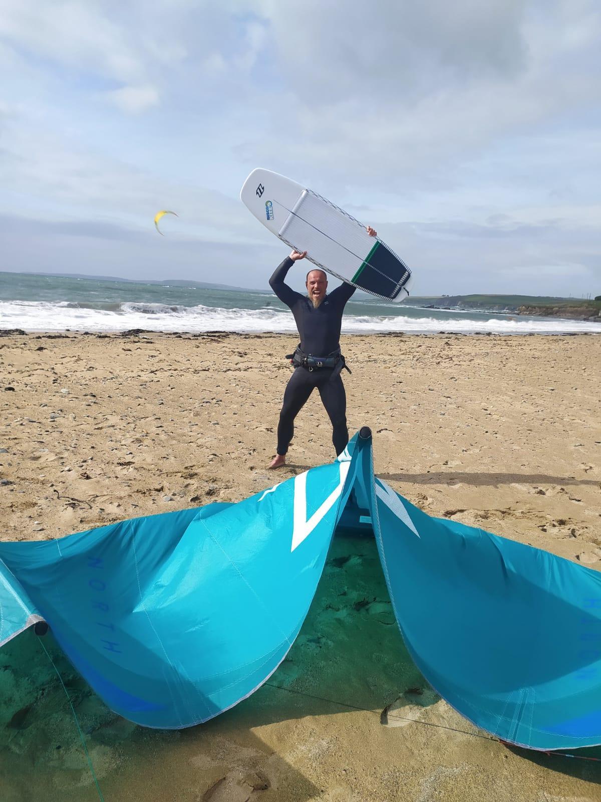 Una persona con una tabla de surf en la playa  Descripción generada automáticamente