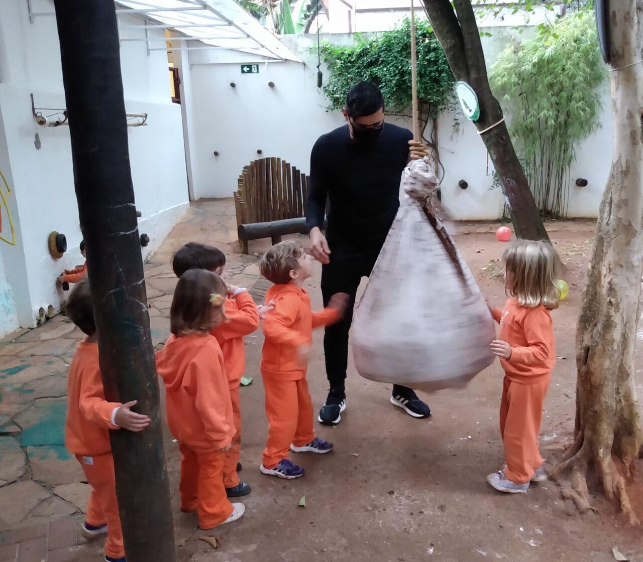 A imagem mostra um adulto vestindo roupa preta segurando na corda de um casulo feito de tecido. O casulo está preso pela corda em uma árvore. Ao redor algumas crianças de roupa cor de laranja observam.