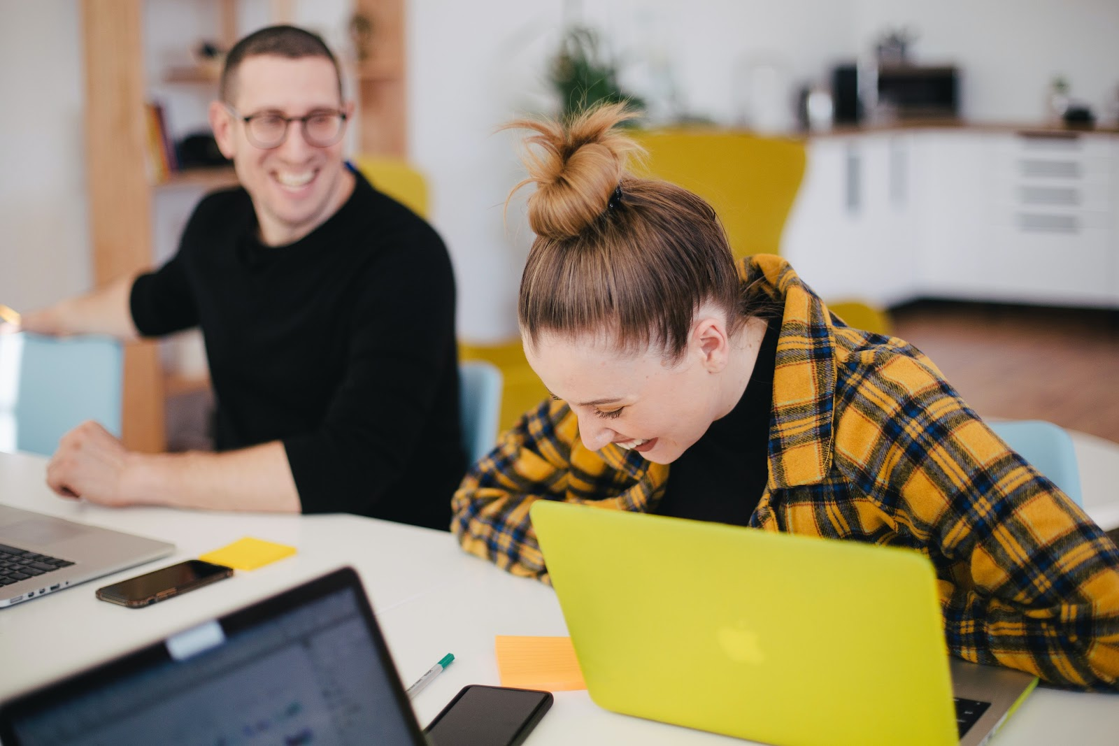 Uma mulher rindo no ambiente de trabalho.