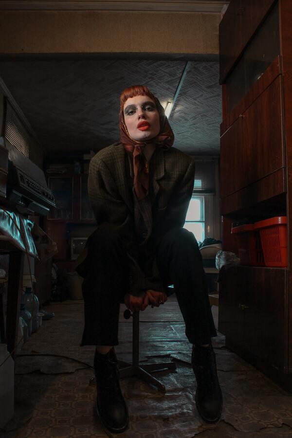 Foto de uma mulher ruiva, sentada e com um lenço na cabeça