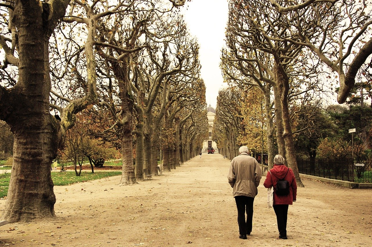 Elderly couple walking in a garden.