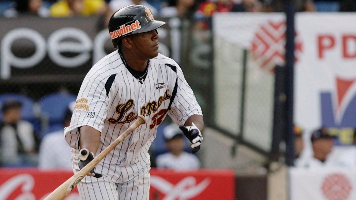 Jugador de béisbol con un bate en la mano  Descripción generada automáticamente