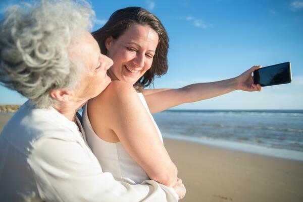Avó e neta abraçadas, na praia, tirando uma selfie.
