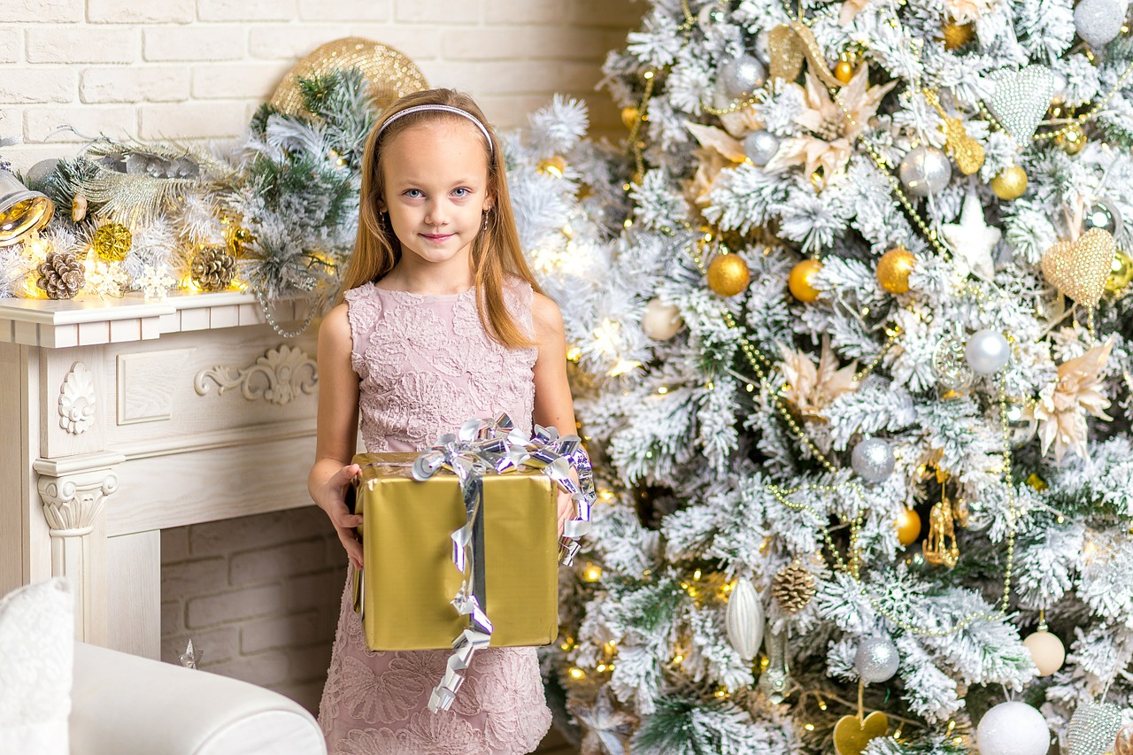 kids packing holiday travel young girl holding gold and silver wrapped present Christmas tree Chicago IL