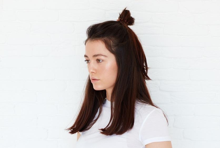 woman wears her dark brown hair half up in a baby bun.