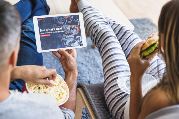Casal comendo e navegando no site da netflix Foto gratuita